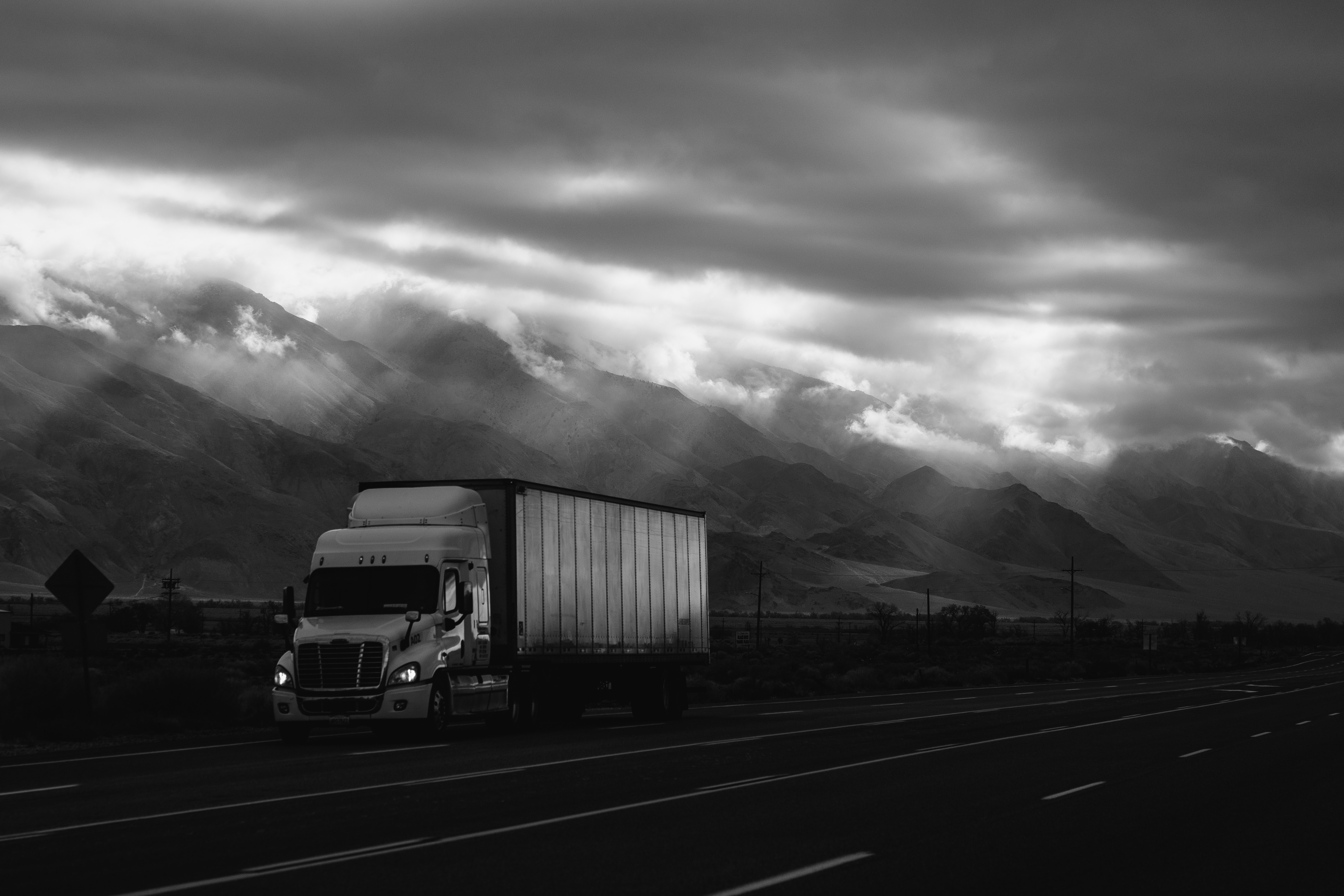 A black and white photo of a truck on the road.