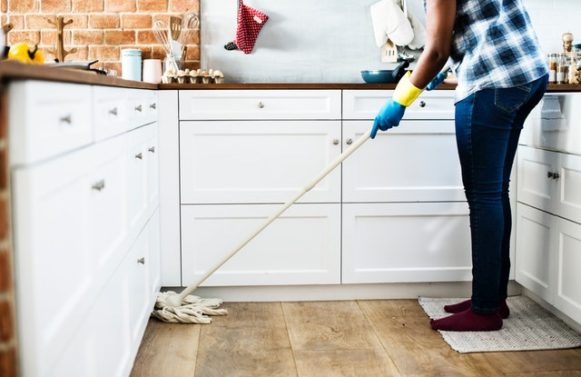 A person cleaning the floor with the mop