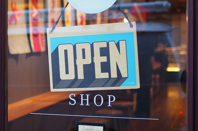 Open shop sign is hanging on the retail store doors