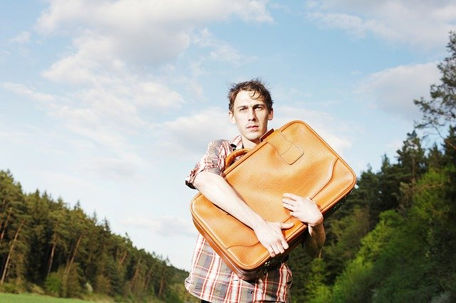 A young man carrying a suitcase as you will be doing when moving from a dorm to your first apartment.