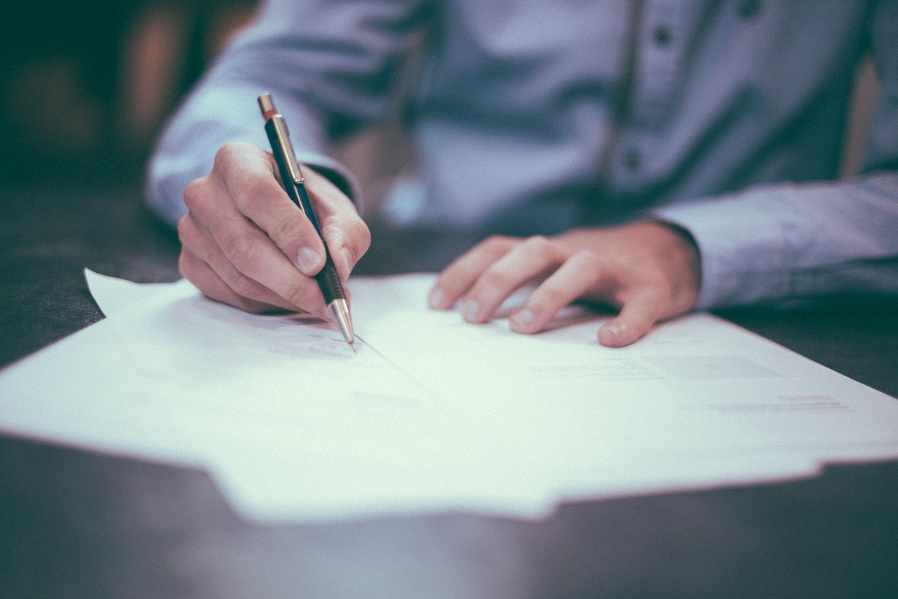 A person signing a commercial lease.